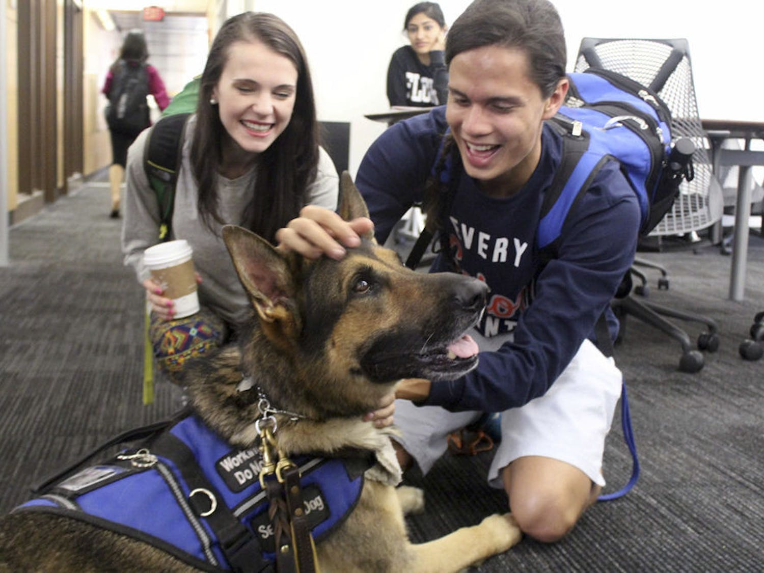Paige Butz and Jason Feliciano, both 20-year-old public relations juniors, play with Zeus the service dog on the second floor of Library West on Wednesday. Zeus visited studying students for Finals Relaxation Week.