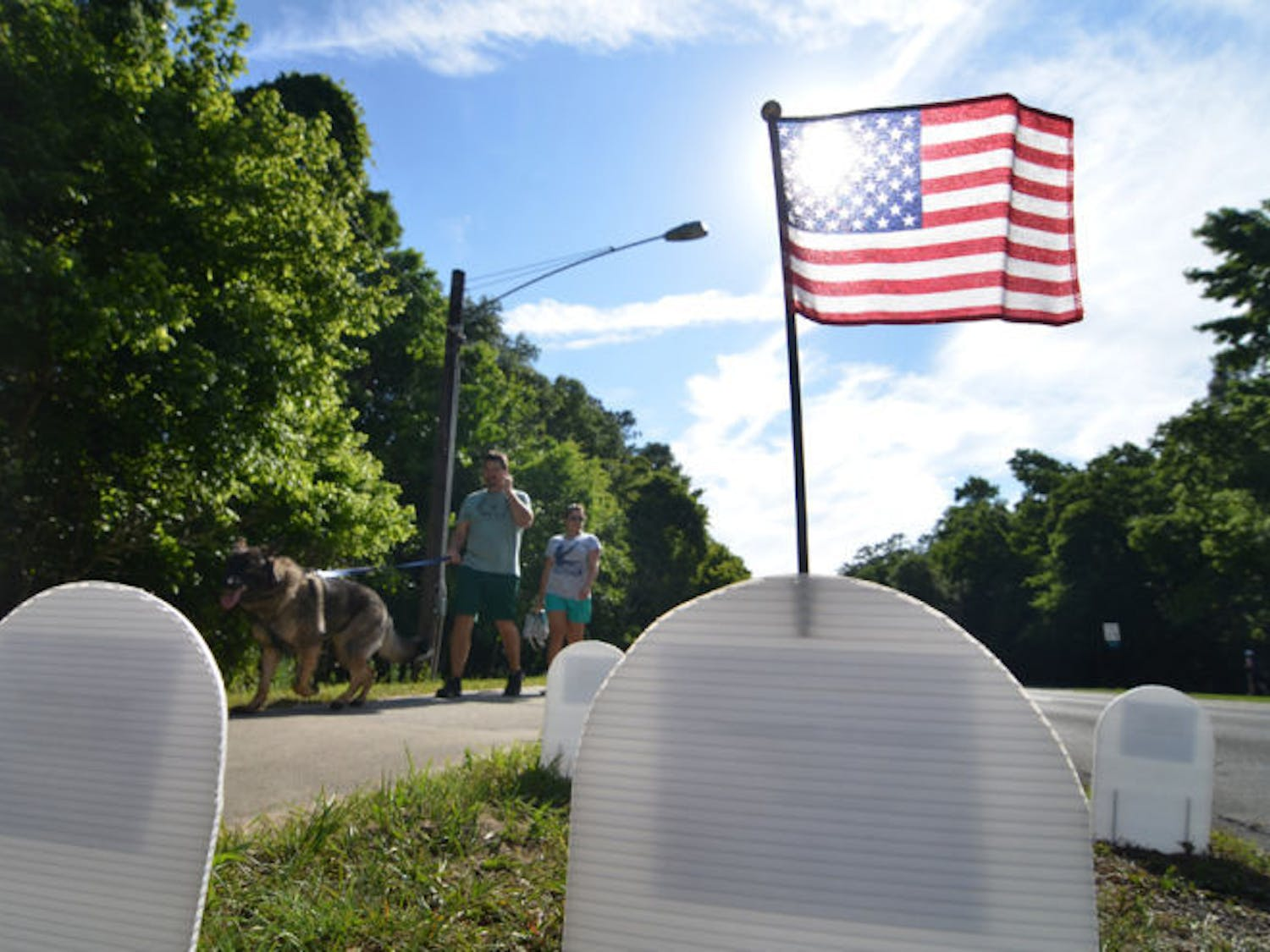 Passers by view thousands of paper tomb stones representing the U.S. Department of Defense Iraq and Afghanistan casualties on NW 8th Avenue on Monday in Gainesville, Fla.
