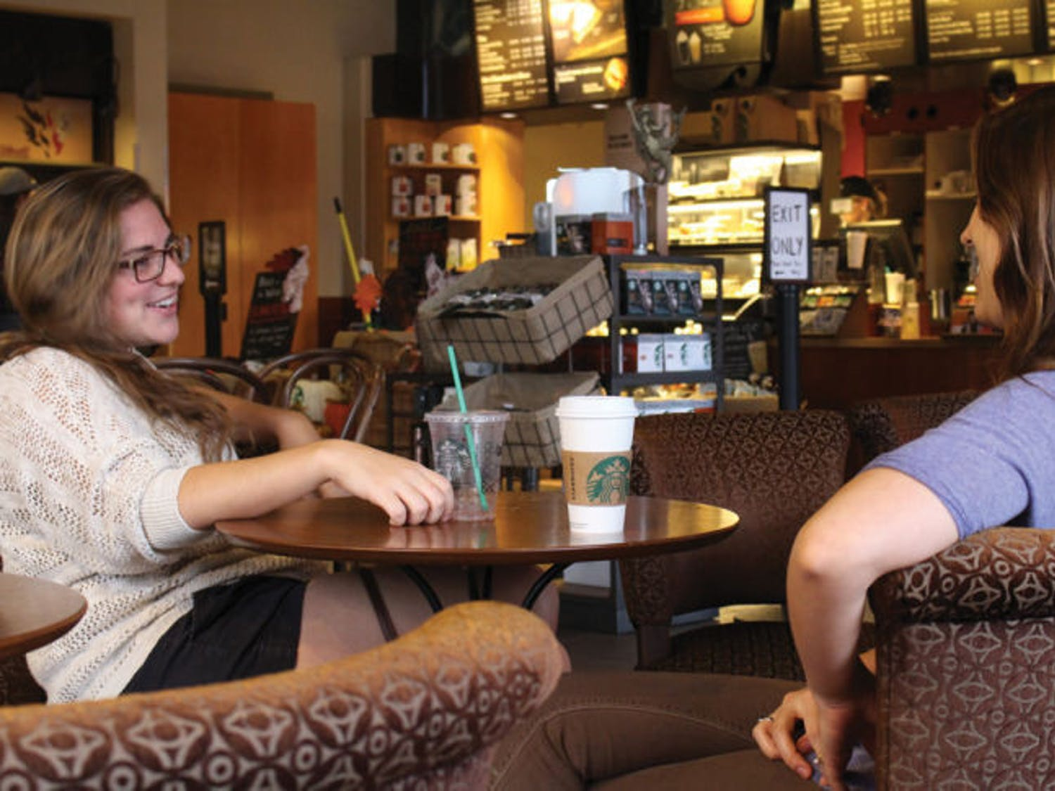 UF economics senior Kerri Stern, 21, left, talks with Gainesville resident Sophie Ouellette-Howitz, 23, Monday at the downtown Starbucks. Starbucks recently asked customers not to bring firearms into its stores.