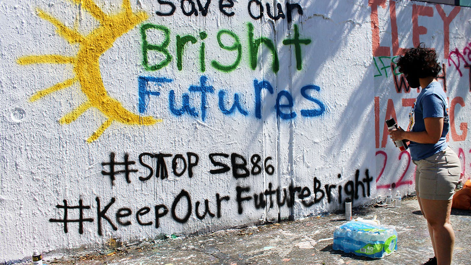 "Alondra Arce, 20, a sustainability sophomore, looks at the ""Save Our Bright Futures"" mural she helped paint on the side of 34th Street in Gainesville on Sunday, March 7, 2021."