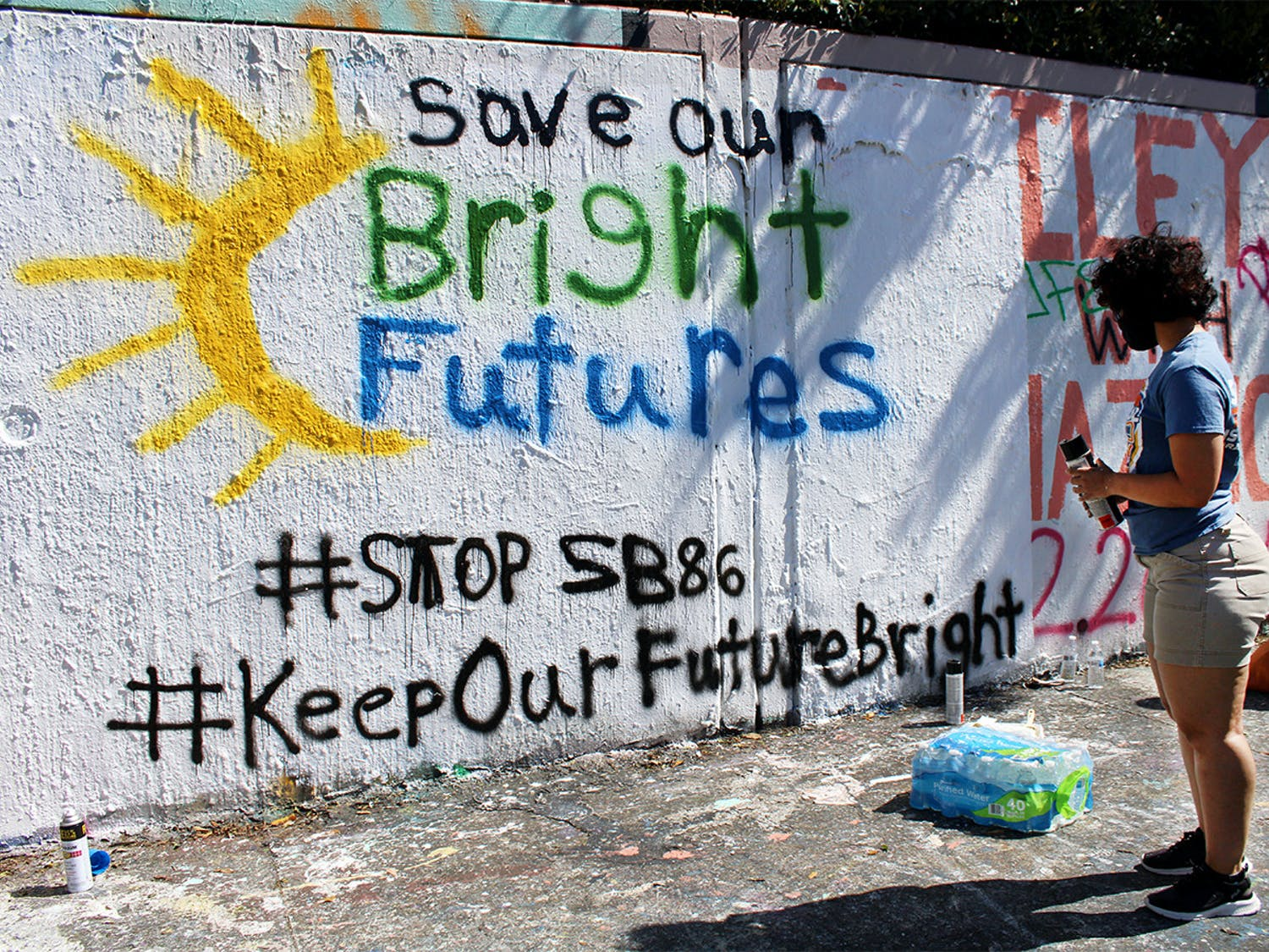 """Alondra Arce, 20, a sustainability sophomore, looks at the """"Save Our Bright Futures"""" mural she helped paint on the side of 34th Street in Gainesville on Sunday, March 7, 2021."""