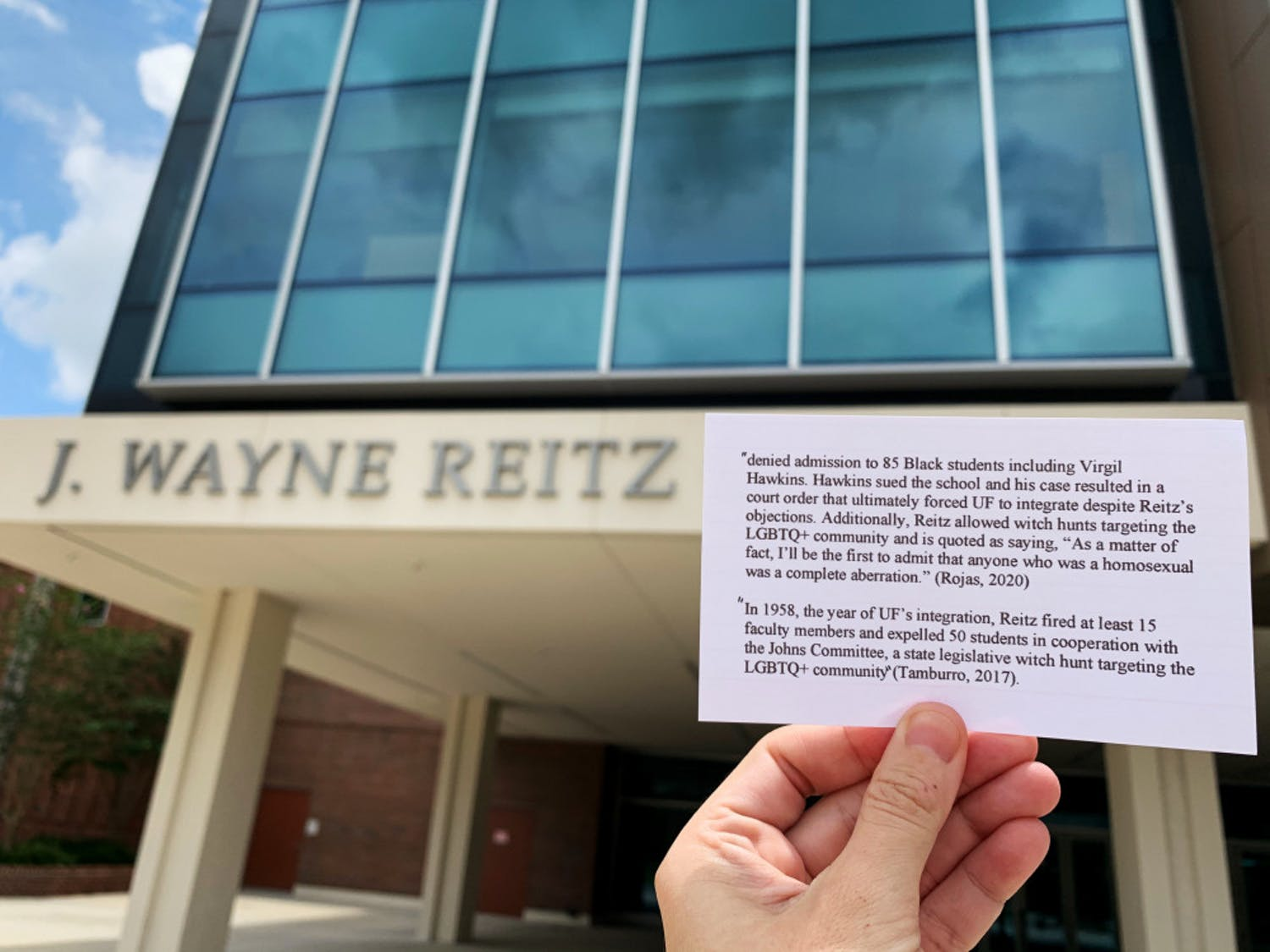 Shelby Boehm, a 28-year-old UF English education Ph.D. student, holds up a piece of paper highlighting J. Wayne Reitz' controversial history with the Reitz Union sign visible in the background. She got the information from Anthony Rojas' petition, andsaid she took the photos while walking around campus becauseshe wanted to do her part in spreading the information to other students and faculty.The photos were posted to Instagram and got hundreds of likes.