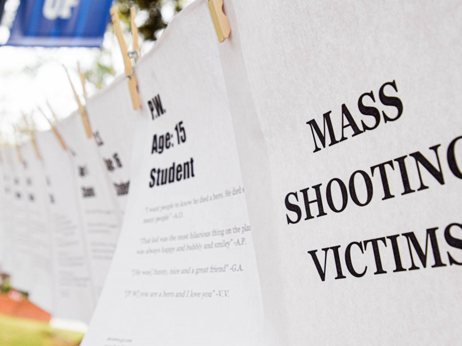 March For Our Lives Gainesville pins up pieces of paper with information about people who died in various mass shootings, such as their name, age and what they were like as told by loved ones.