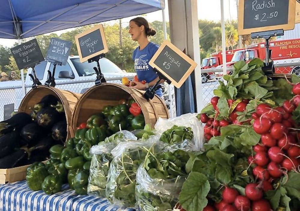 <p>The Family Garden sells their produce at the Alachua County Farmers Market on Oct. 26. Now, they're watching unsold produce rot in their fields due to COVID-19.</p>
