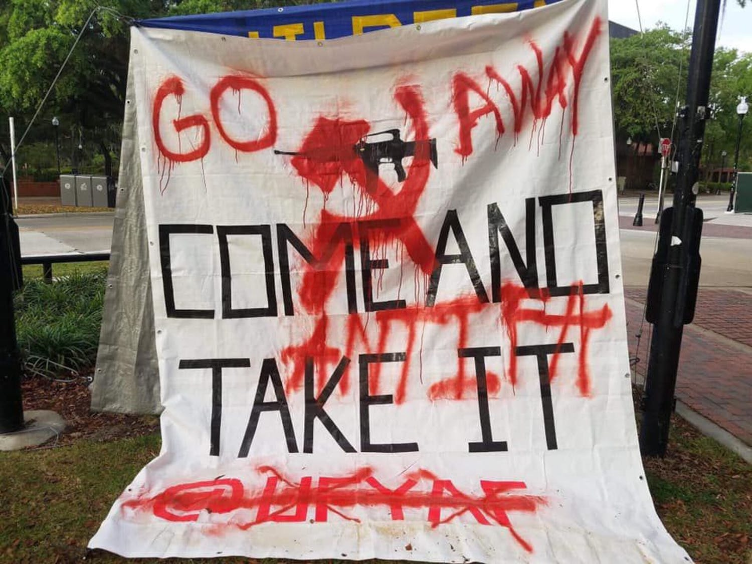 "UF's Young Americans for Freedom gun rights banner hangs on Plaza of the Americas Saturday morning after being spray painted with the words ""Go away"" by an unknown vandalist."