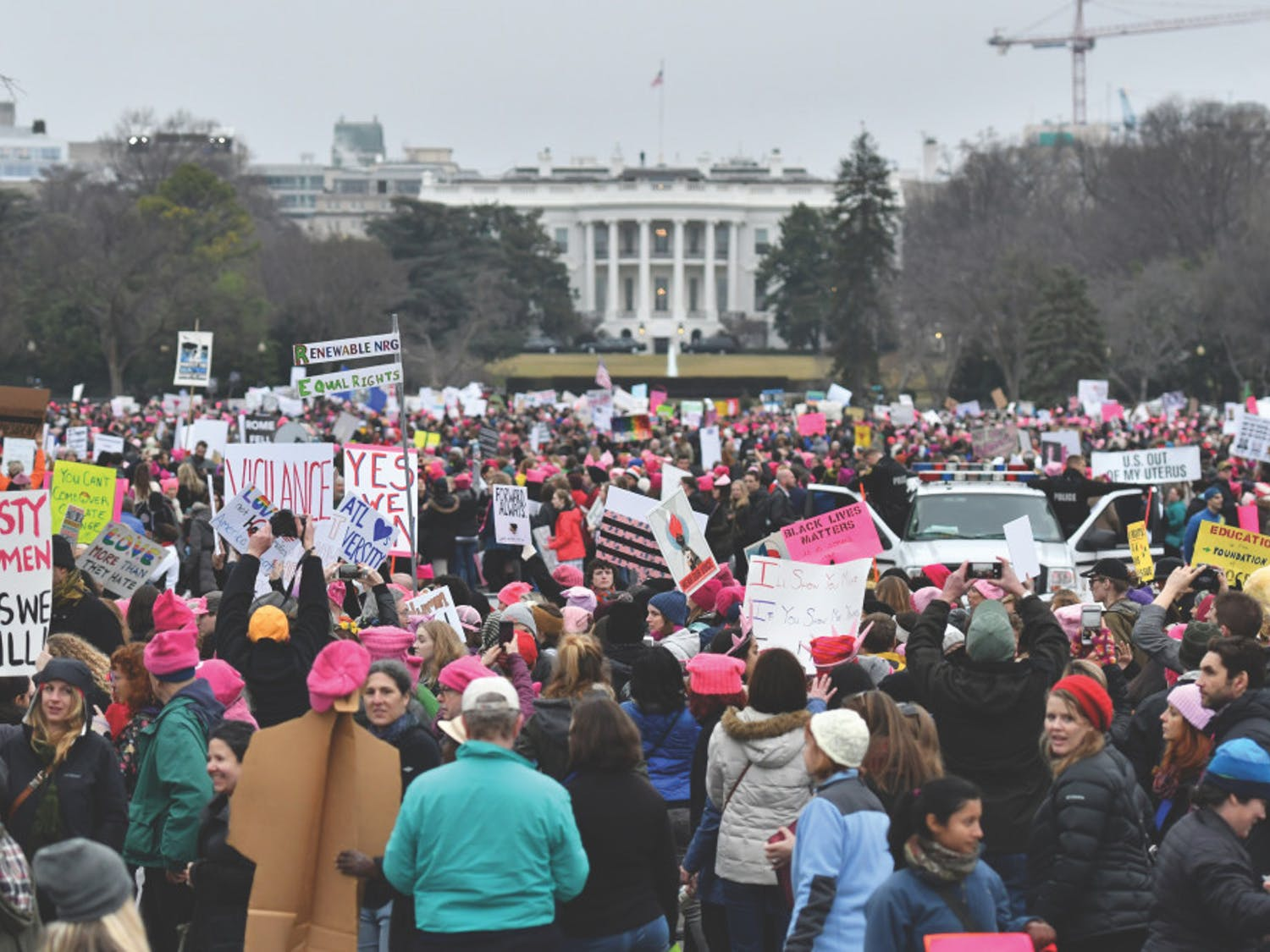 """Thousands gather on the Ellipse near the back lawn of the White House at the conclusion of the Women's March on Washington. Many of the marchers placed their posters along a few small fences to create """"walls"""" near the White House."""