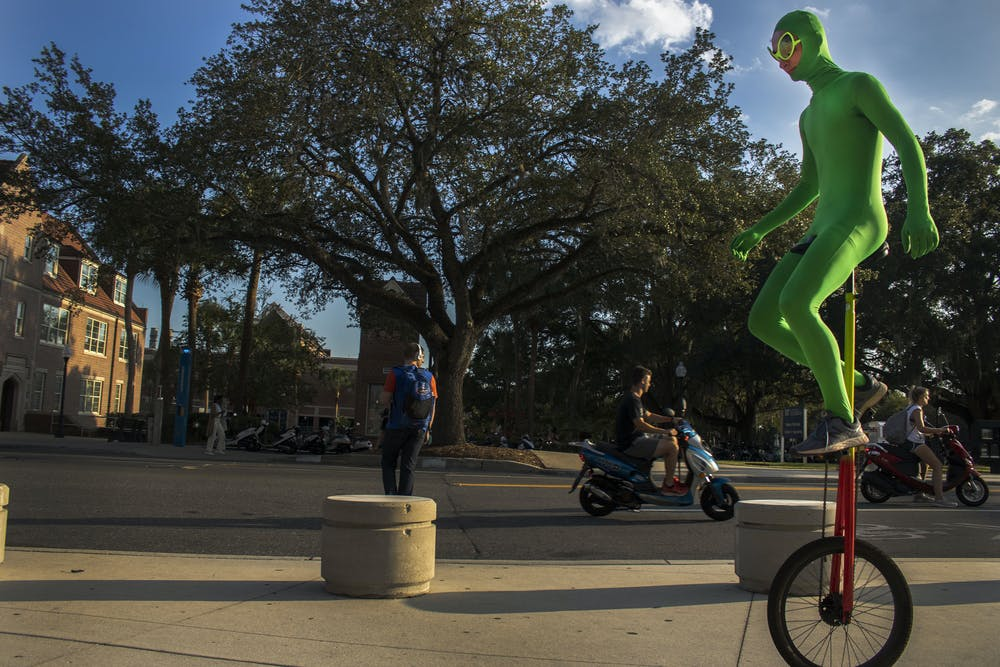 """<p dir=""""ltr""""><span>Ethan Gamble, 17-year-old Gainesville High student, rides his unicycle down Stadium Road while wearing his green alien outfit. Gamble said he first started by riding around the bus loop at JJ Finley Elementary school. """"You just have to practice,"""" Gamble said. """"Until you get the feel of it.""""</span></p><p><span></span></p>"""
