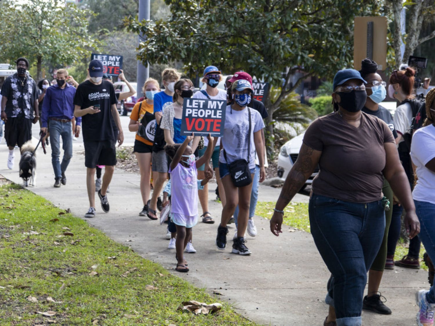 "People are seen holding ""Let My People Vote"" signs at the ""Free the Vote"" rally while walking away from Bo Diddley Plaza on Saturday, Oct. 24, 2020."