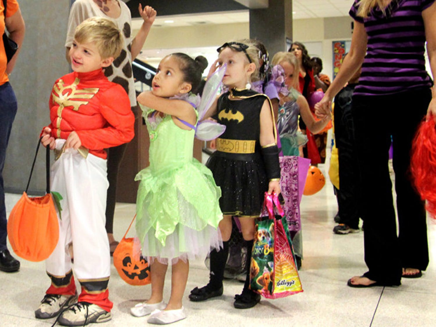 A Baby Gator pre-kindergarten class lines up outside of the Game Room at the Reitz Union to get treats from manager Charlotte Dare on Thursday. Parents donated candy for the trick-or-treating adventure.
