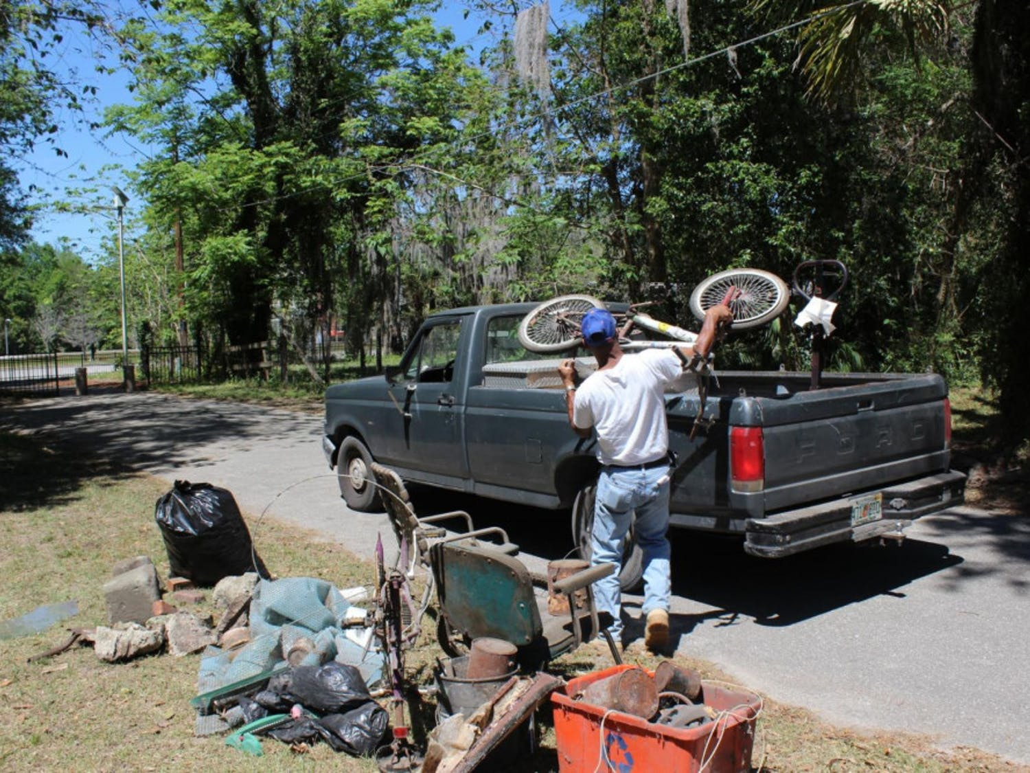Mitchell George, 54, loads his pickup truck with a rusted bicycle outside an elderly Gainesville woman's home on Saturday. George, who lives in the city's Porters Community, hauled away junk UF students cleared from the woman's home as a part of UF Student Government's inaugural The Big Event, a service day involving about 760 students and about 45 locations throughout Gainesville.