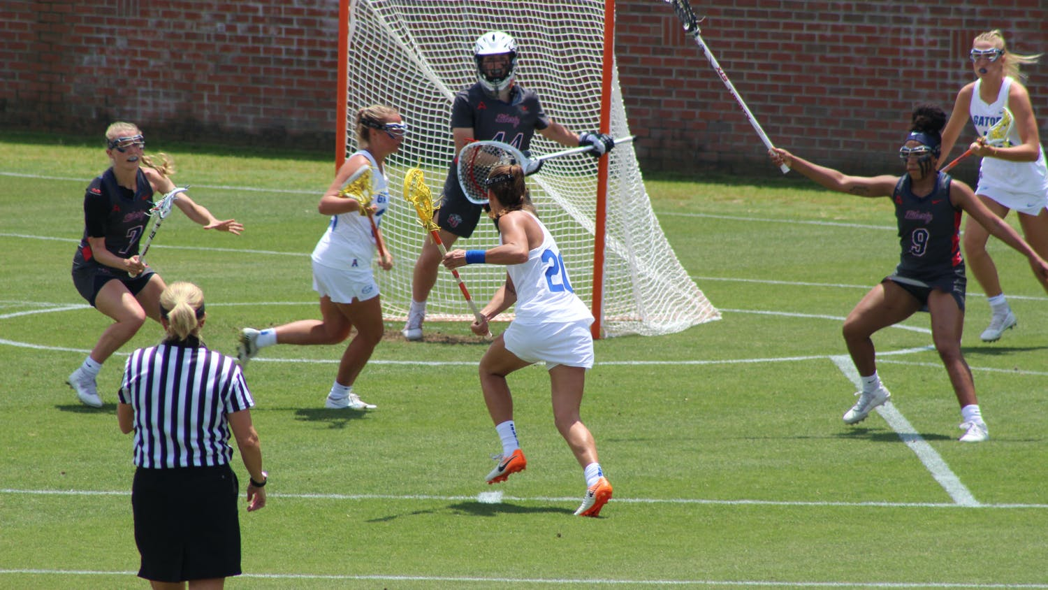 Florida attacker Brianna Harris (No. 20, center) cradles and advances towards Liberty's goal on April 28. The Gators ended their regular season with an 11th straight victory over the Flames, 17-2, to end the year 14-2.