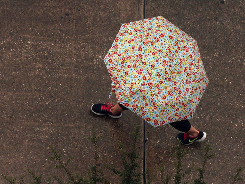 A Nike-wearing umbrella holder takes strides down Stadium Road in the rain on Monday.