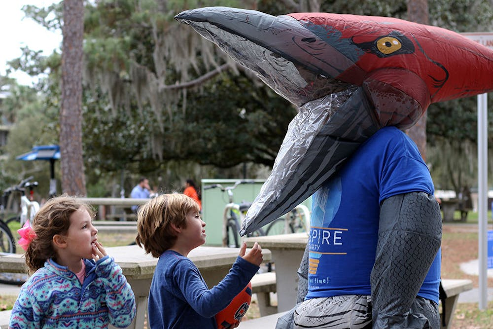 "<p dir=""ltr""><span>Mary Katherine Boney, 5, and Hampton Boney, 7, inspect Zachariah Chou's Inspire-themed dinosaur costume Tuesday outside of the The Hub. Chou, a 21-year-old UF political science junior, is Inspire Party's presidential candidate for the 2019 UF Student Government elections. Inspire Party members also dressed up in a Pikachu outfit while campaigning. Chou said that the idea for the inflatable outfits came from the ""'Pokemon Go' to the polls"" statement that Hillary Clinton made during the 2016 presidential election. ""We thought it would be a very positive way to increase voter turnout, and it's definitely something different,"" he said. ""It all started with the Pikachu suit.""</span></p> <p><span>&nbsp;</span></p>"