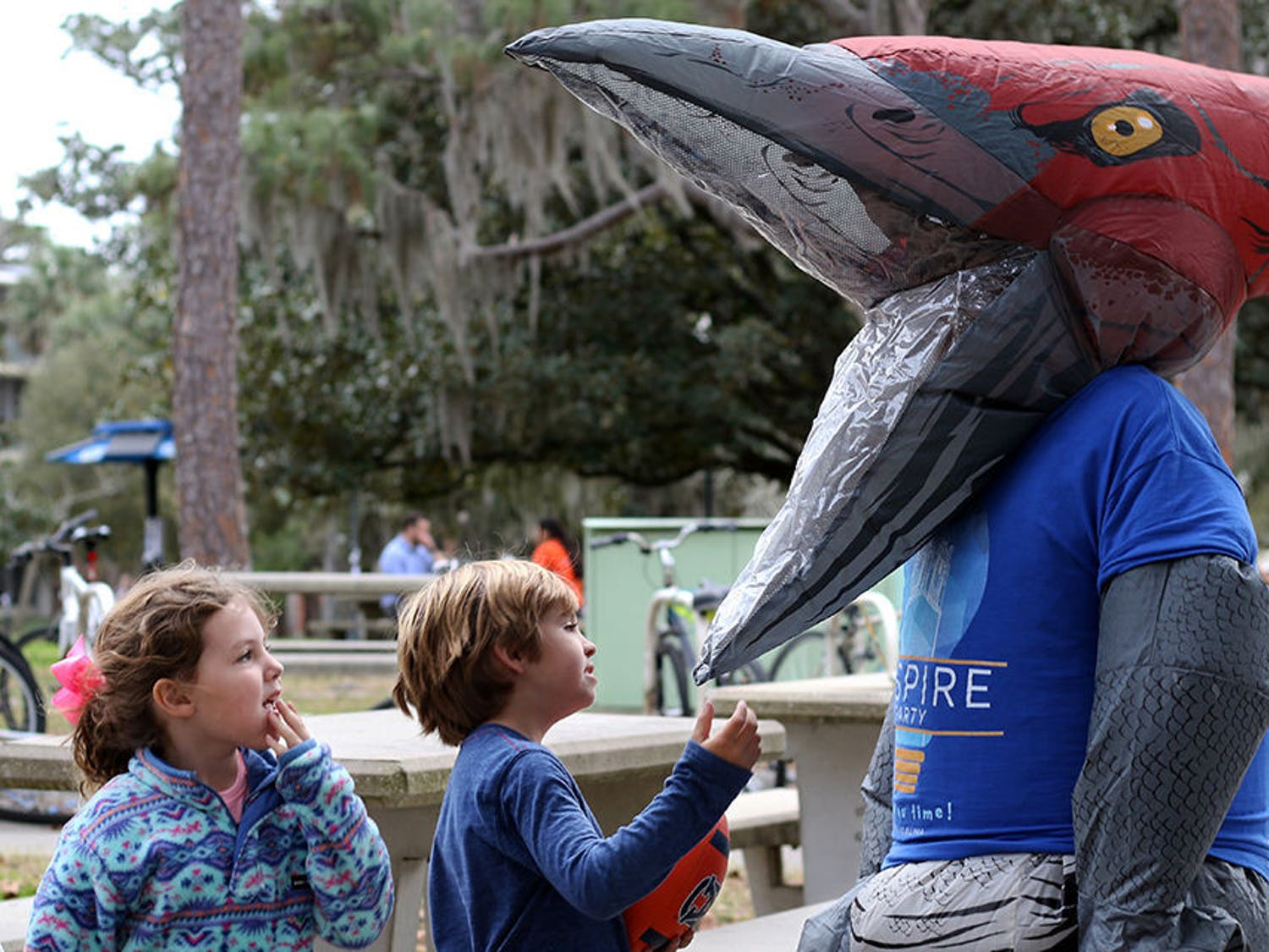 "Mary Katherine Boney, 5, and Hampton Boney, 7, inspect Zachariah Chou's Inspire-themed dinosaur costume Tuesday outside of the The Hub. Chou, a 21-year-old UF political science junior, is Inspire Party's presidential candidate for the 2019 UF Student Government elections. Inspire Party members also dressed up in a Pikachu outfit while campaigning. Chou said that the idea for the inflatable outfits came from the ""'Pokemon Go' to the polls"" statement that Hillary Clinton made during the 2016 presidential election. ""We thought it would be a very positive way to increase voter turnout, and it's definitely something different,"" he said. ""It all started with the Pikachu suit."""