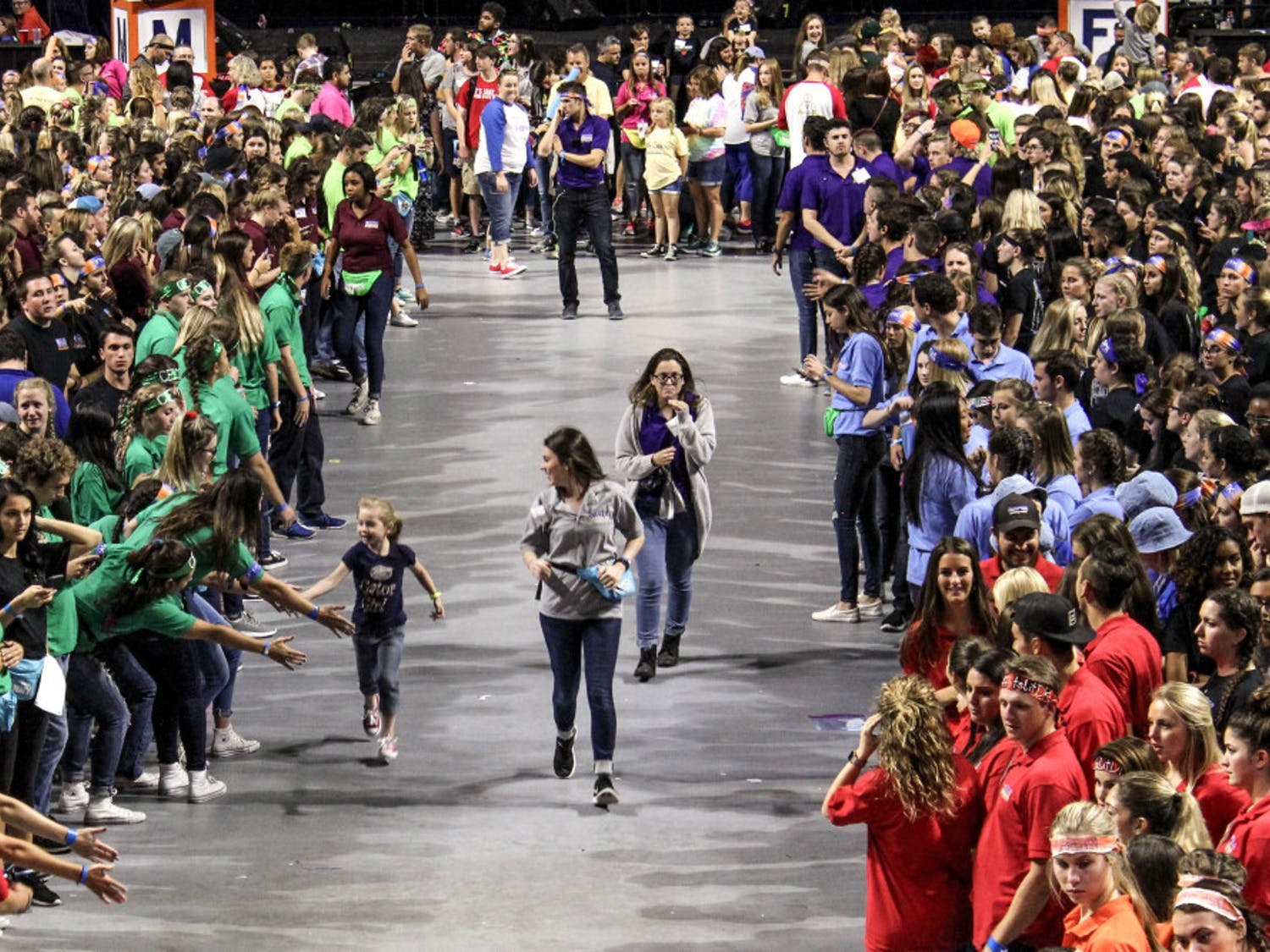 A child runs through the crowd of dancers during Dance Marathon at the O'Connell Center on Sunday. Dance Marathon is an event where volunteers must stay awake and on their feet for 26.2 hours.