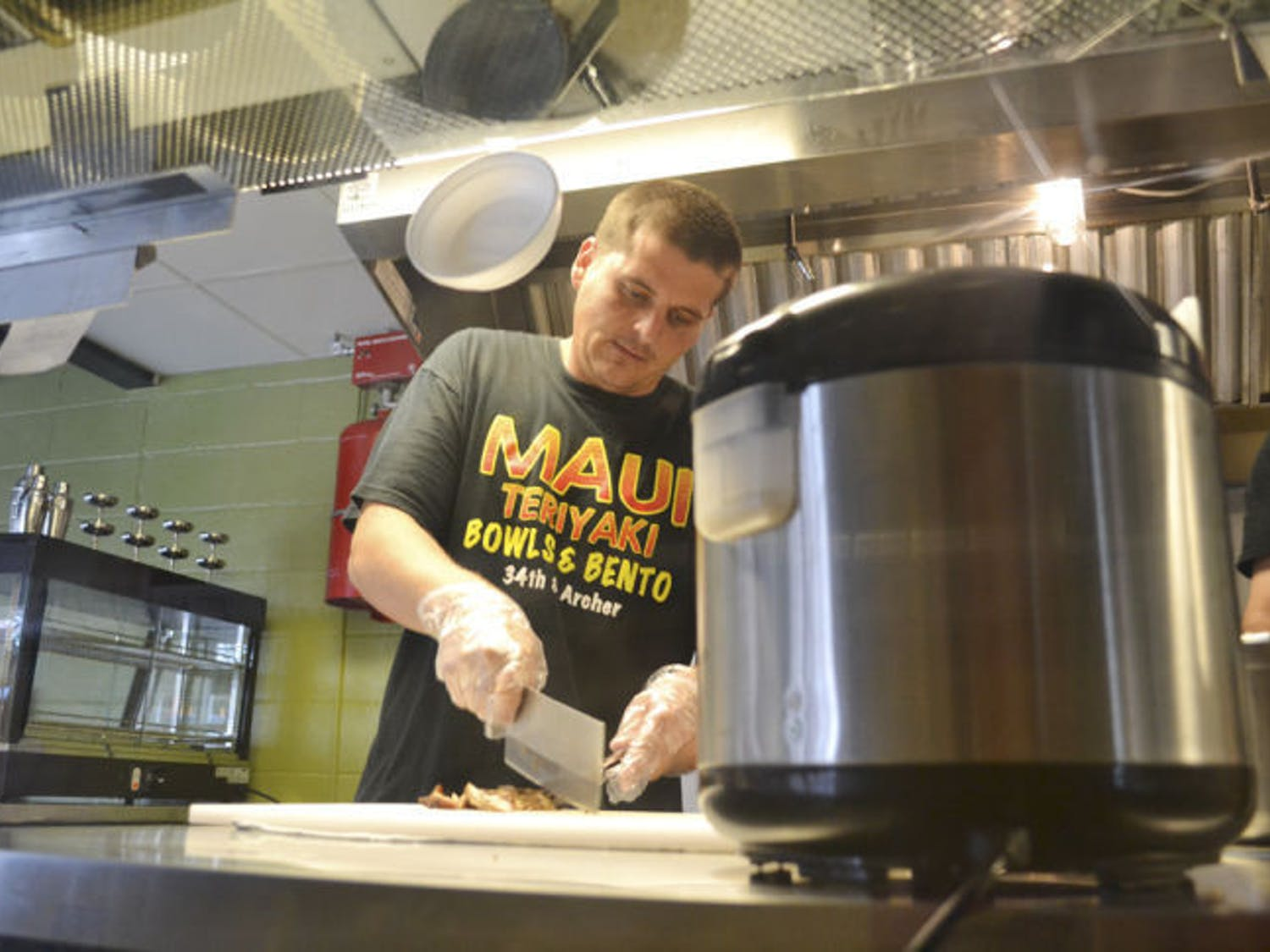 Gainesville native and Maui Grill manager Justin Amerson, 29, makes the Classic Chicken Bowl on Wednesday evening. The new restaurant opened April 21, replacing Corner - Latin Confusion.