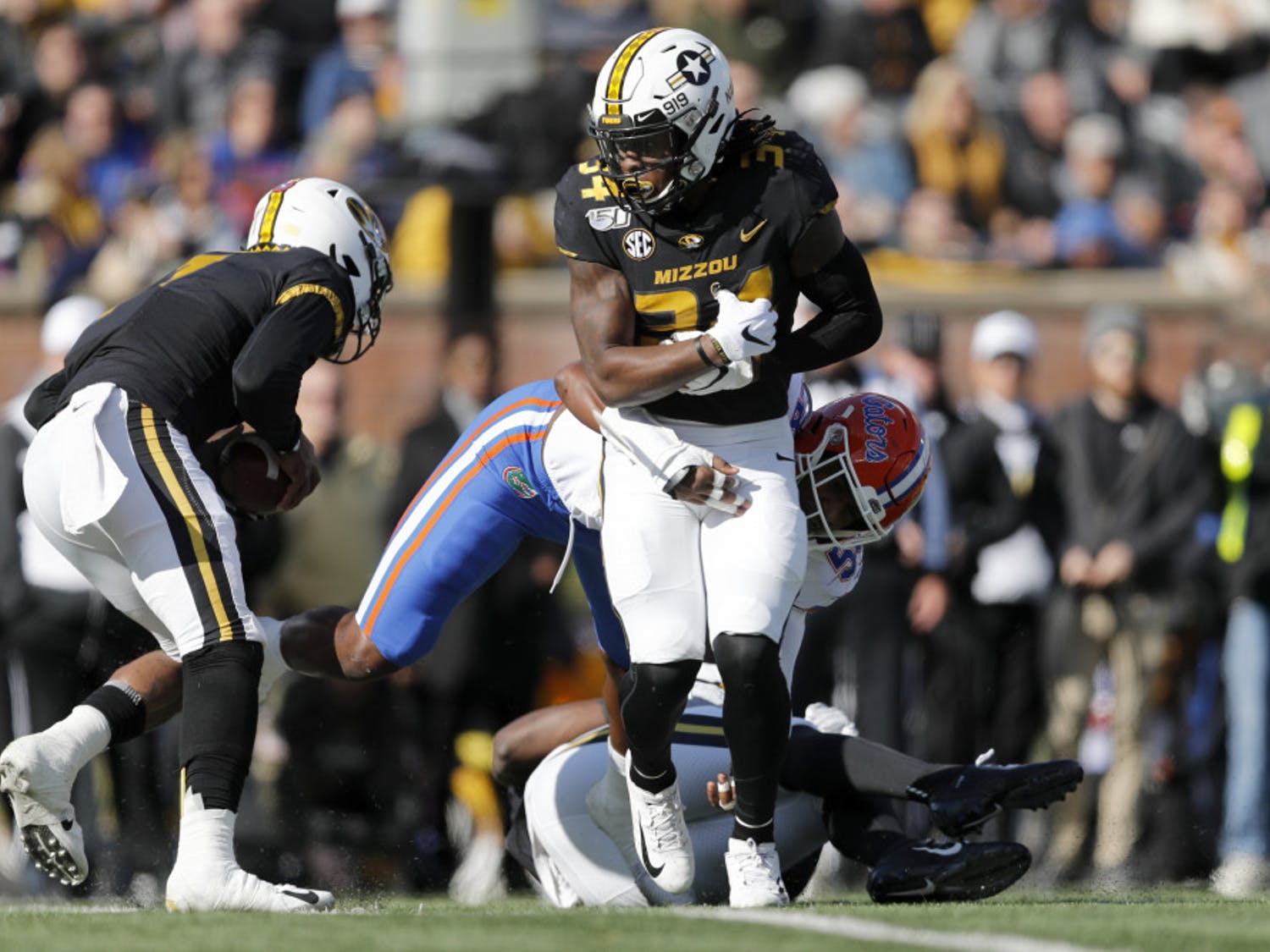 Missouri running back Larry Rountree III, front, struggles for yardage before being pulled down by Florida linebacker Jonathan Greenard during the first half of an NCAA college football game Saturday, Nov. 16, 2019, in Columbia, Mo. (AP Photo/Jeff Roberson)