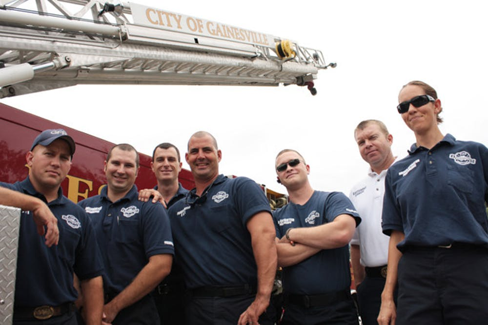 """<p>Firefighters from B shift at Station 1,427 S Main St., pose with """"Quint,"""" their backup aerial fire truck. Firefighters said they have the utmost respect for law enforcement officers who lost their lives on Sept. 11, 2001.</p>"""