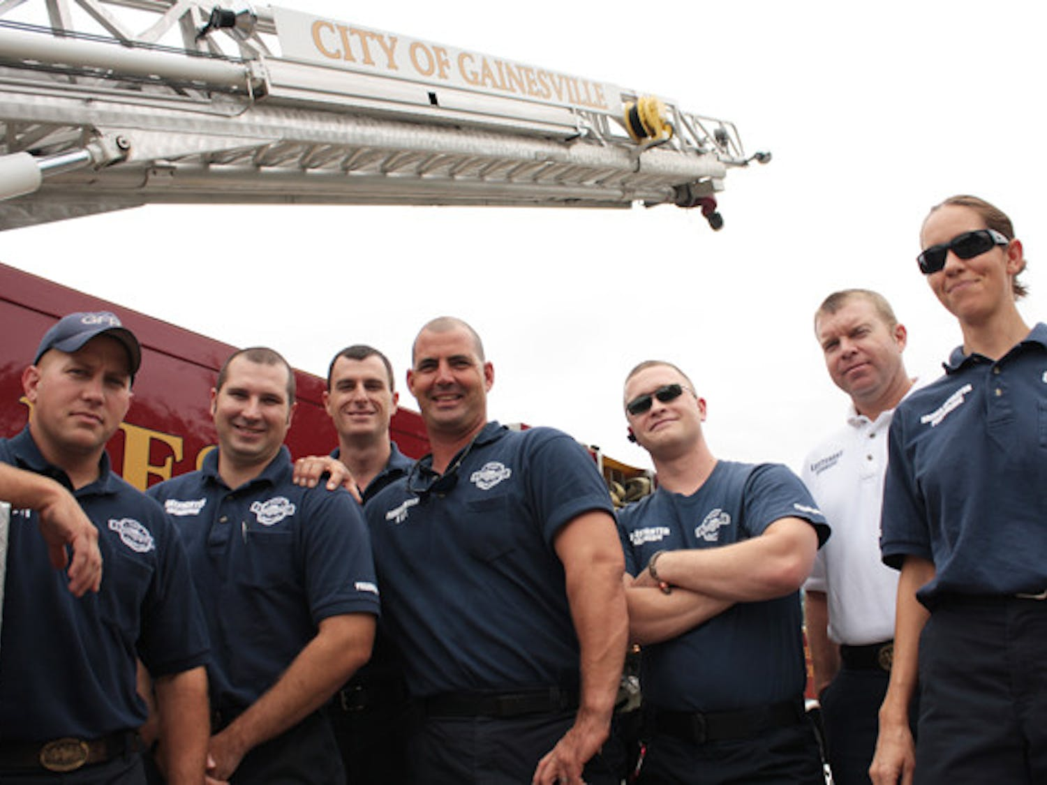 """Firefighters from B shift at Station 1,427 S Main St., pose with """"Quint,"""" their backup aerial fire truck. Firefighters said they have the utmost respect for law enforcement officers who lost their lives on Sept. 11, 2001."""