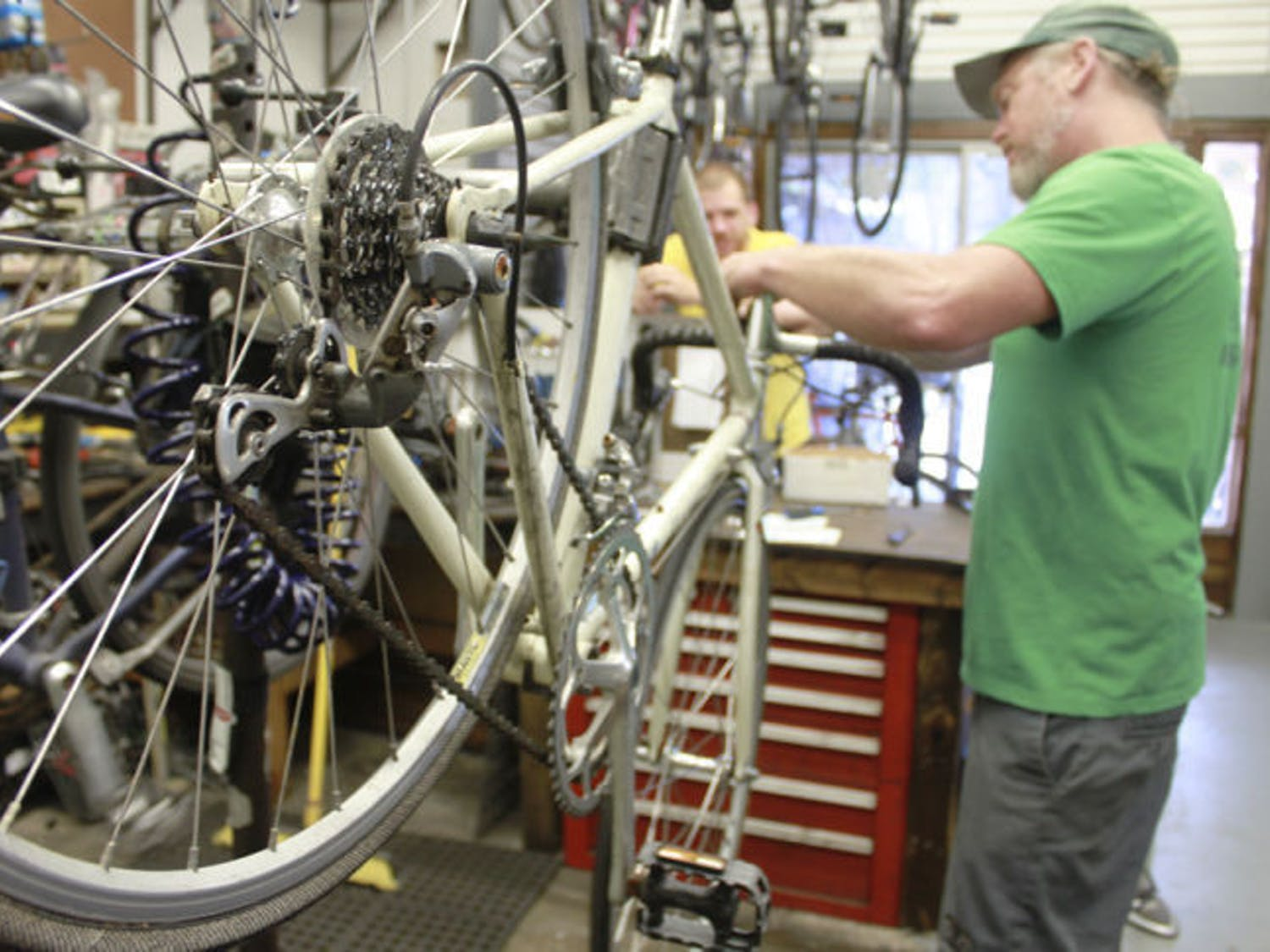 Mike Hetrick, 47, owner of Goodbike, works on a vintage Fuji road bike on Wednesday. The shop at 425 NW 13th St. opened its doors with a new name and new management on the Fourth of July.