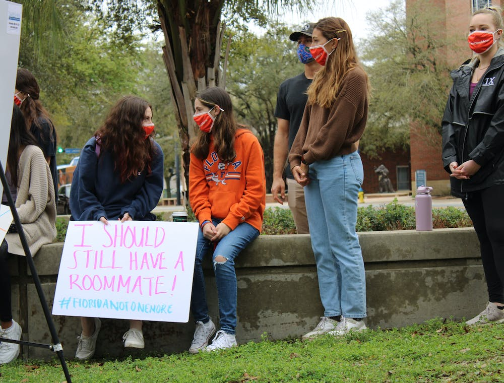 "Sydney Kaskin (left), 19, a neuroscience freshman and former roommate of Sophia Lambert holds a sign that says ""I should still have a roommate!"" as she speaks with another member of the Florida Not One More student group during a press conference on Wednesday, March 3, 2021. The press conference was held by two attorneys representing the families of Sophia Lambert and Maggie Paxton in two wrongful death lawsuits that were recently filed."