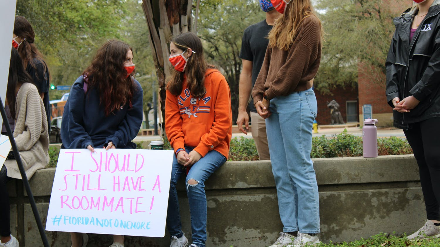 """Sydney Kaskin (left), 19, a neuroscience freshman and former roommate of Sophia Lambert holds a sign that says """"I should still have a roommate!"""" as she speaks with another member of the Florida Not One More student group during a press conference on Wednesday, March 3, 2021. The press conference was held by two attorneys representing the families of Sophia Lambert and Maggie Paxton in two wrongful death lawsuits that were recently filed."""