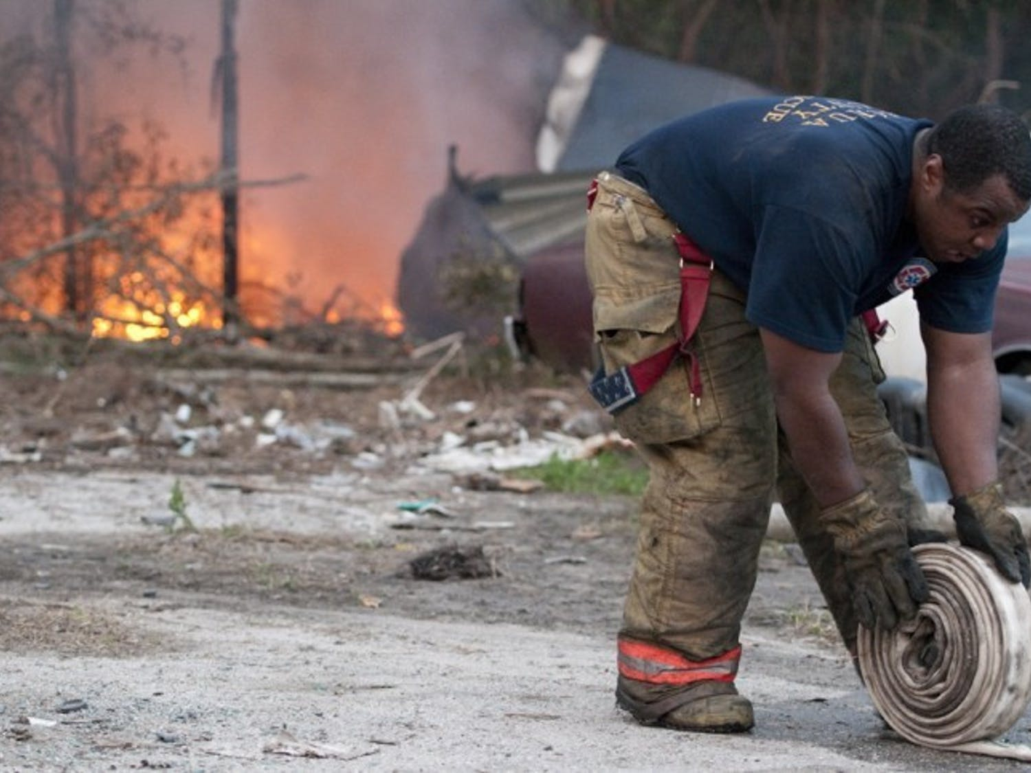 An Alachua County Fire Rescue Worker packs up equipment at 3530 SE Hawthorne Road after tending to a commercial tire fire Tuesday evening.
