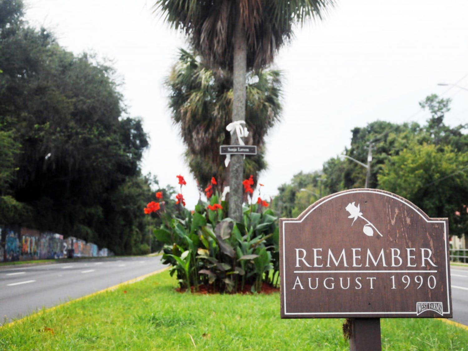 "A sign that reads ""Remember August 1990"" stands in the median of Southwest 34th Street. Behind it stands five trees with white ribbons and the names of the five students killed by Danny Rolling. This week marked the 25th anniversary of the murders."