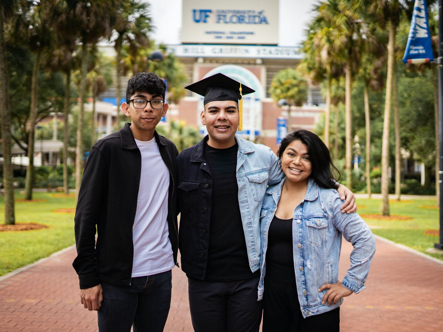 Jose Alvarez, center, and siblings David and Ismelda Alvarez, left and right, celebrate Jose's graduation from the University of Florida in front of the Ben Hill Griffin Stadium.