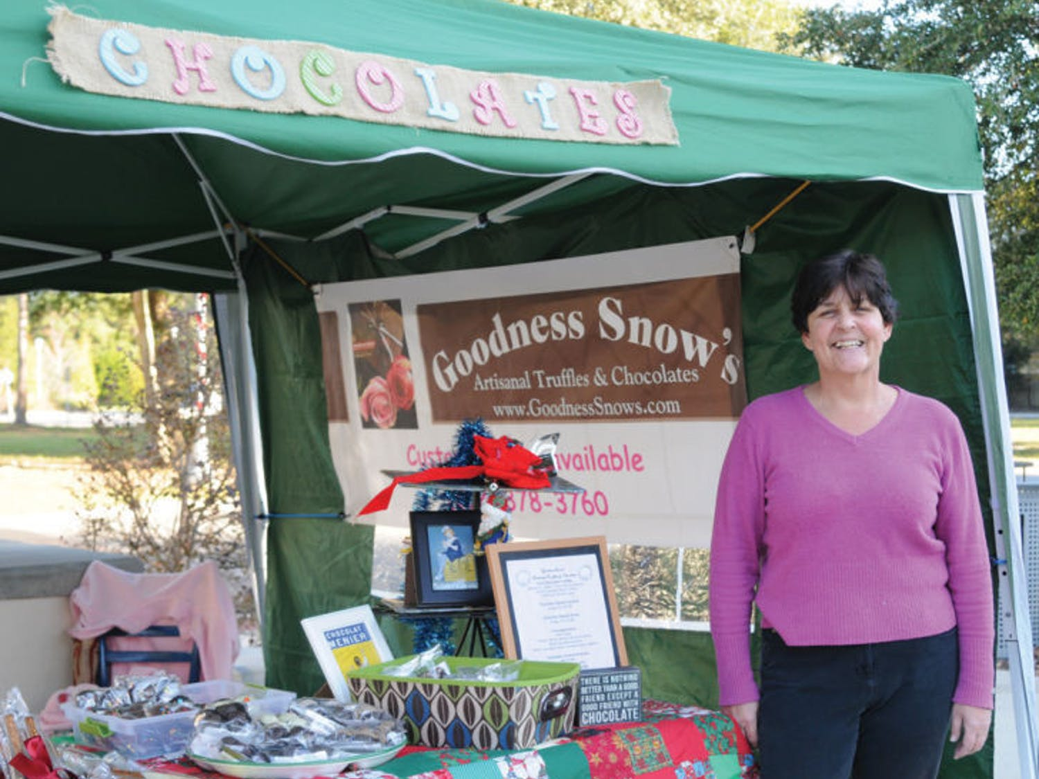 Gwen Thompson, owner of Goodness Snow's, smiles next to the stand she and her husband sell their chocolates from. They frequently set up shop in the Tioga Town Center from 3 to 6 p.m. on Monday afternoons.