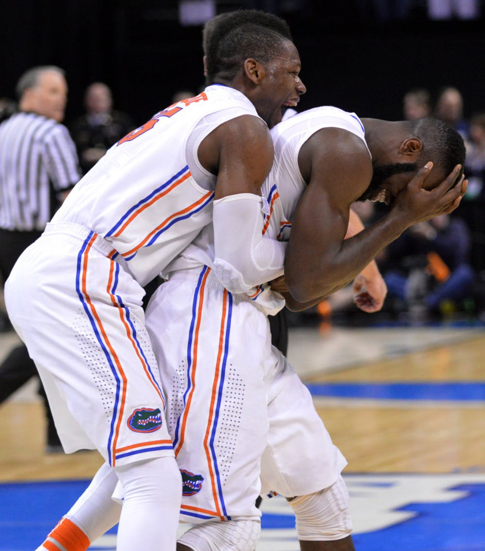 <p>Will Yeguete jumps on teammate Patric Young's back in celebration following Florida's 62-52 win against Dayton on Saturday in FedEx Forum in Memphis, Tenn.</p>