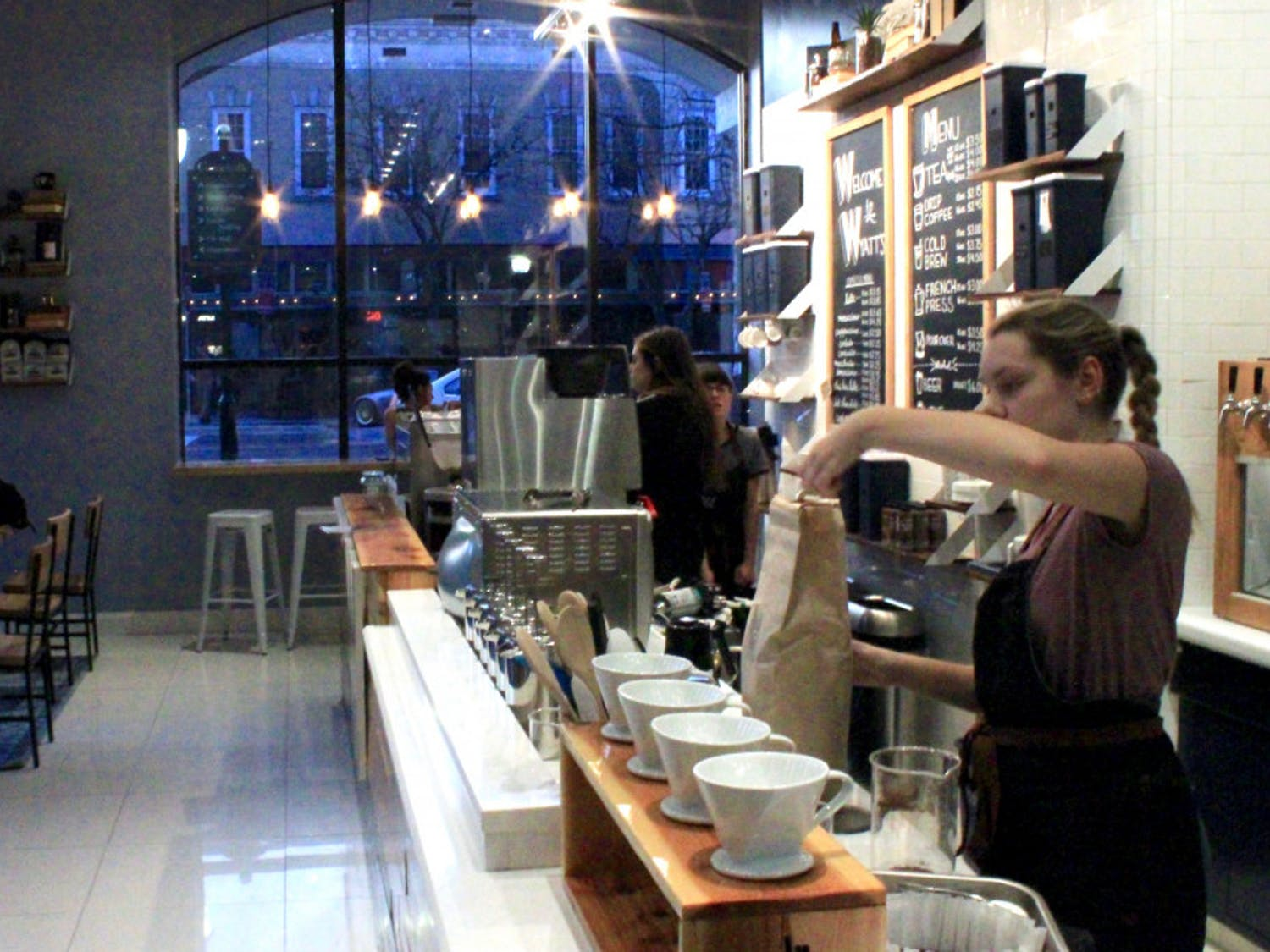 Emily Hart, a 20-year-old UF psychology student, scoops fresh coffee grounds from a bag on Sunday afternoon at Wyatt's Coffee's new downtown location at 202 SE Second Ave.