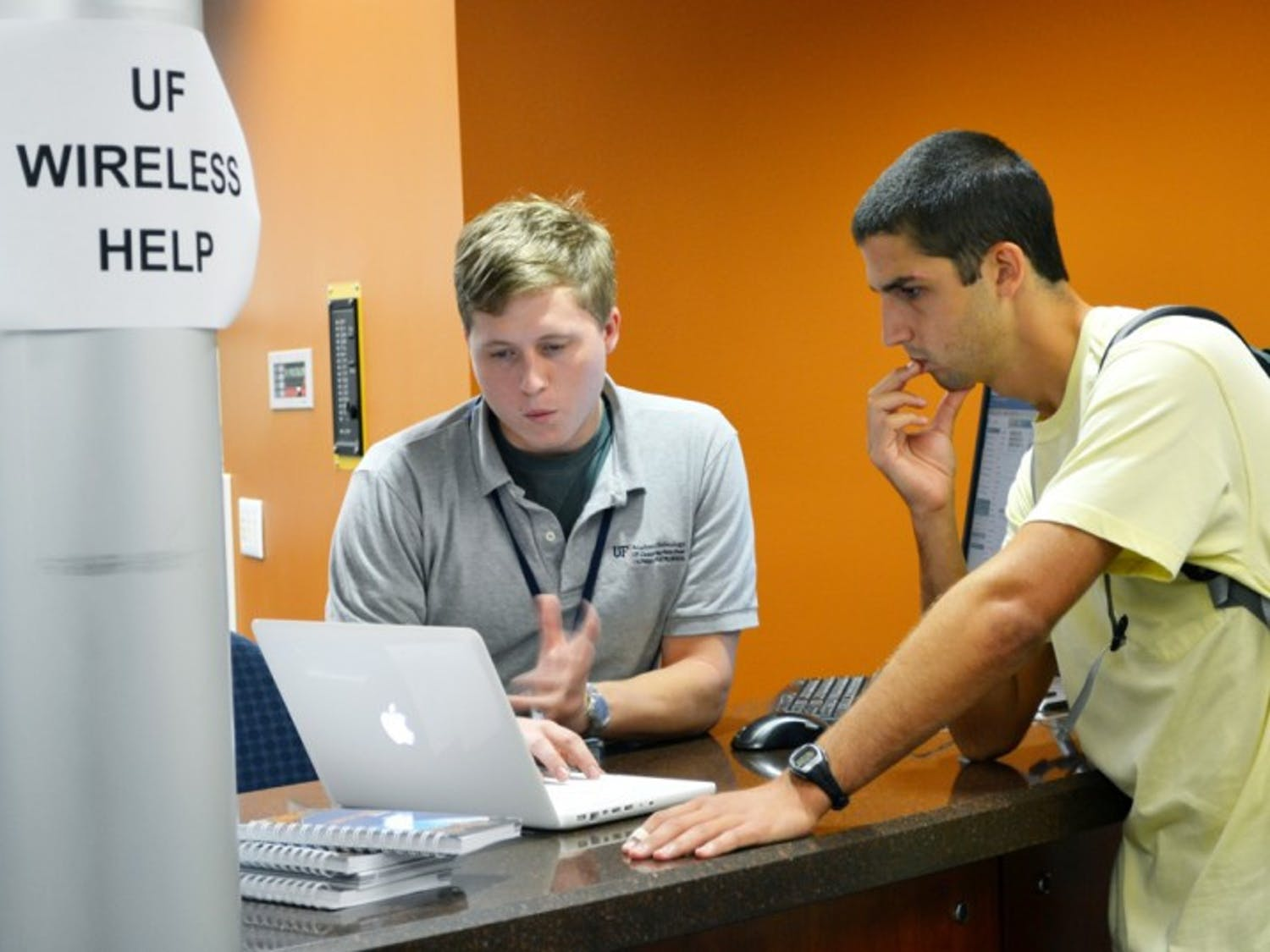 Todd Lowen, a 20-year-old telecommunication sophomore, gets help from Kellen Denny, a Computing Help Desk associate, on Thursday. Lowen had problems with his MacBook's wireless internet after moving to campus.