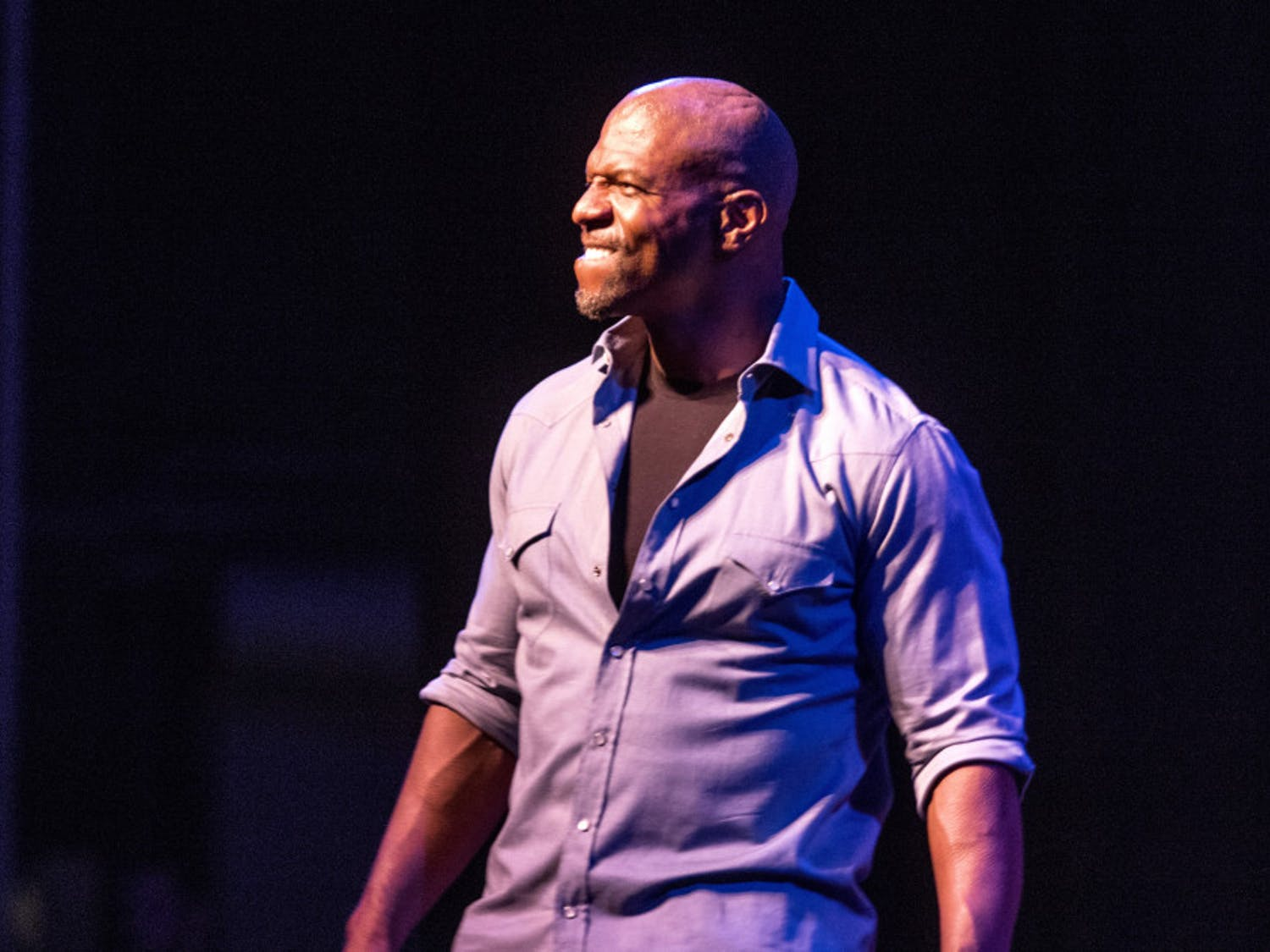 Terry Crews smiles for the crowd as he makes an enthusiastic entrance inside the Phillips Center for the Performing Arts on Tuesday night at the Accent Speakers Bureau-hosted event. Crews shared stories of rejection and perseverance along his journey of success.