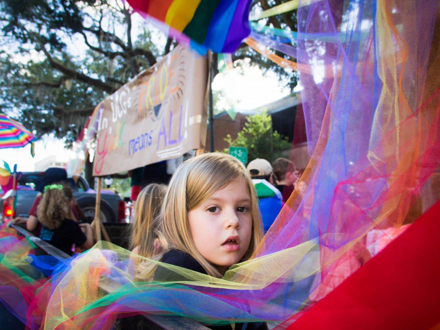 """Seven-year-old Elizabeth Poe, daughter of Gainesville Mayor Lauren Poe, sits on a parade float Saturday afternoon during the the Gainesville Pride Parade. """"Pride gets bigger and better and more celebratory every year,"""" Mayor Poe said."""