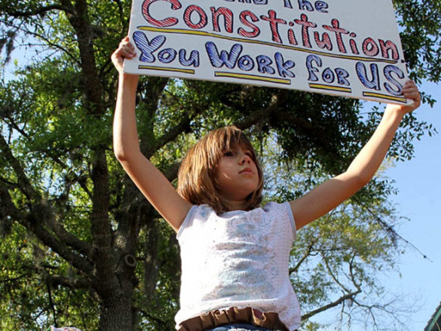 Alyssa, 9, holds a sign at the Tea Party rally in the Bo Diddley Downtown Community Plaza on Thursday afternoon.