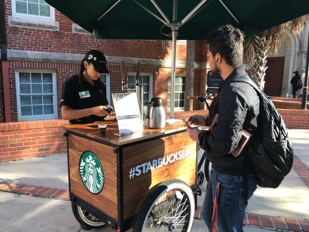 """<p dir=""""ltr""""><span>Irfan Kovankaya, a 21-year-old UF political science junior, stops by the #StarbucksBIKE to buy a cup of nitro cold brew coffee before class.</span></p><p><span></span></p>"""