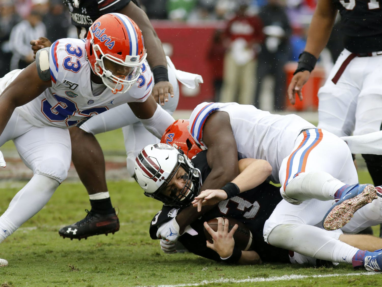 South Carolina's Ryan Hilinski, bottom, gets sacked by Florida's Zachary Carter, right, in the first half of an NCAA college football game Saturday, Oct. 19, 2019, in Columbia, SC. Florida defeated South Carolina 38-27.