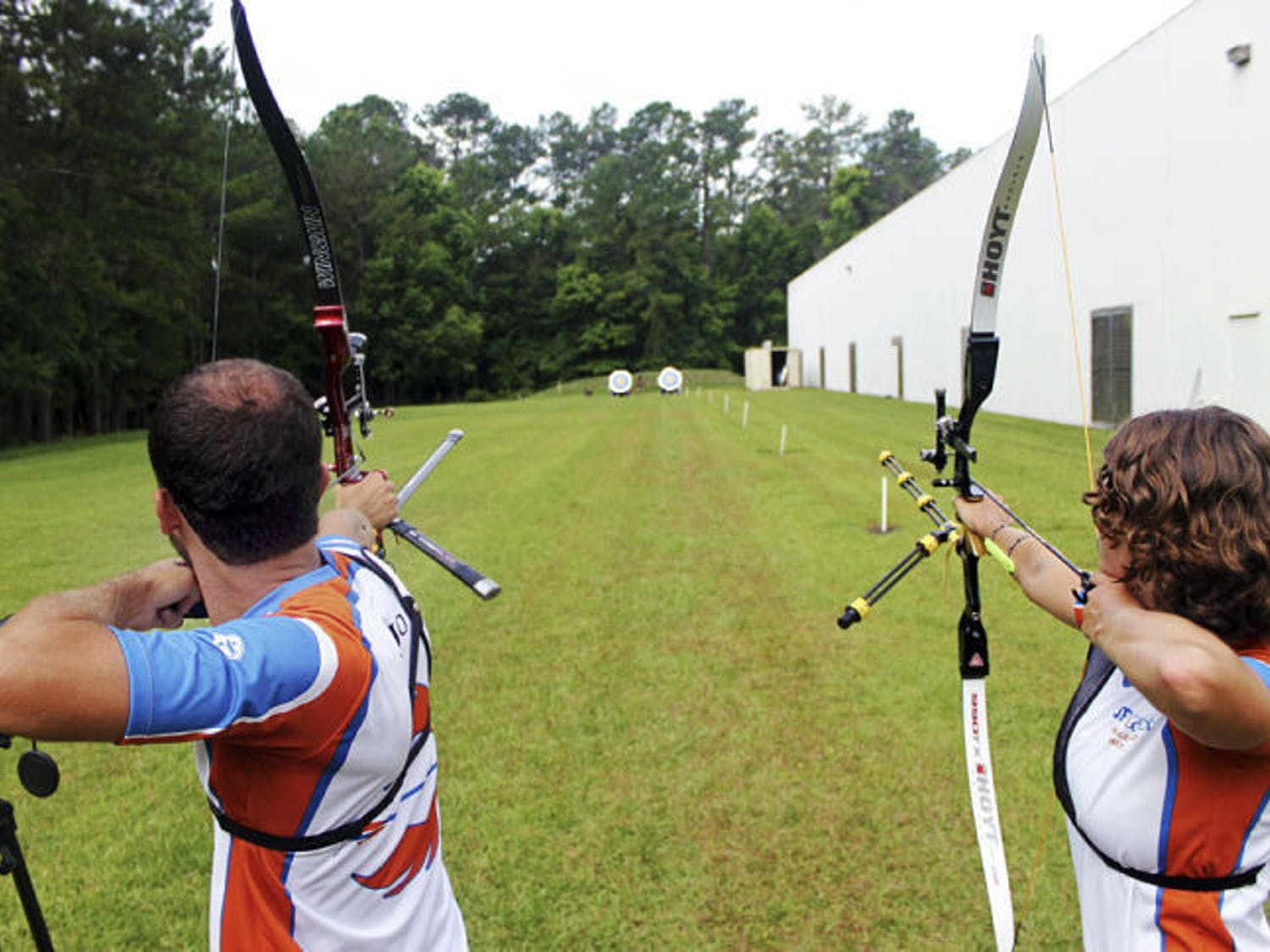 Robert Regojo and Rachel Bouchillon, a 22-year-old UF environmental science graduate student, practice on a range behind Bear Archery's headquarters in Gainesville.