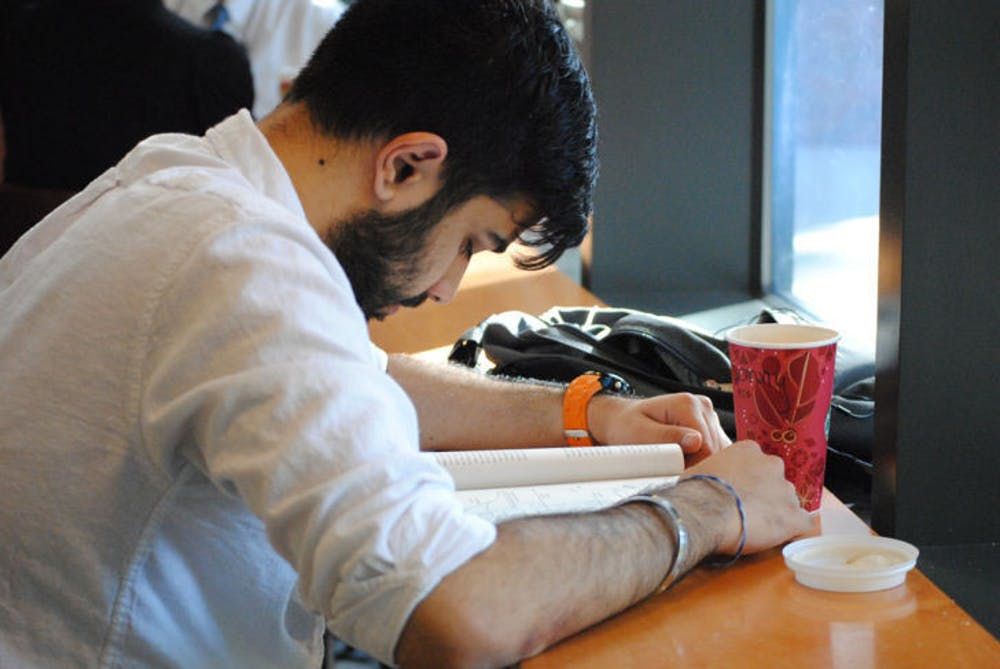 <p>Sundeep Singh, 20, drinks coffee while studying at the Library West Starbucks on Wednesday afternoon. Recent studies suggest people do not regularly consume coffee during the hours that would have the strongest effect.</p>