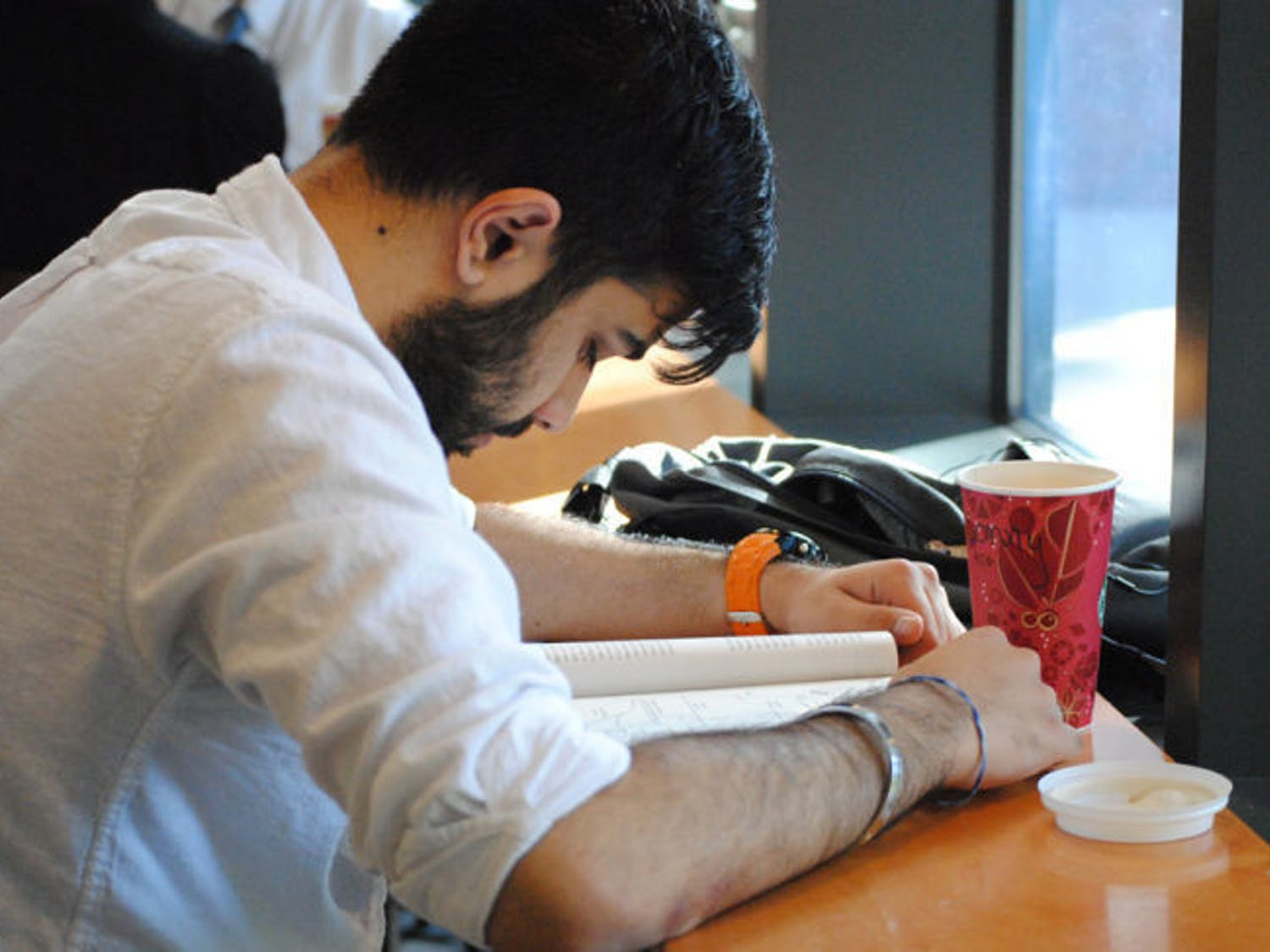 Sundeep Singh, 20, drinks coffee while studying at the Library West Starbucks on Wednesday afternoon. Recent studies suggest people do not regularly consume coffee during the hours that would have the strongest effect.