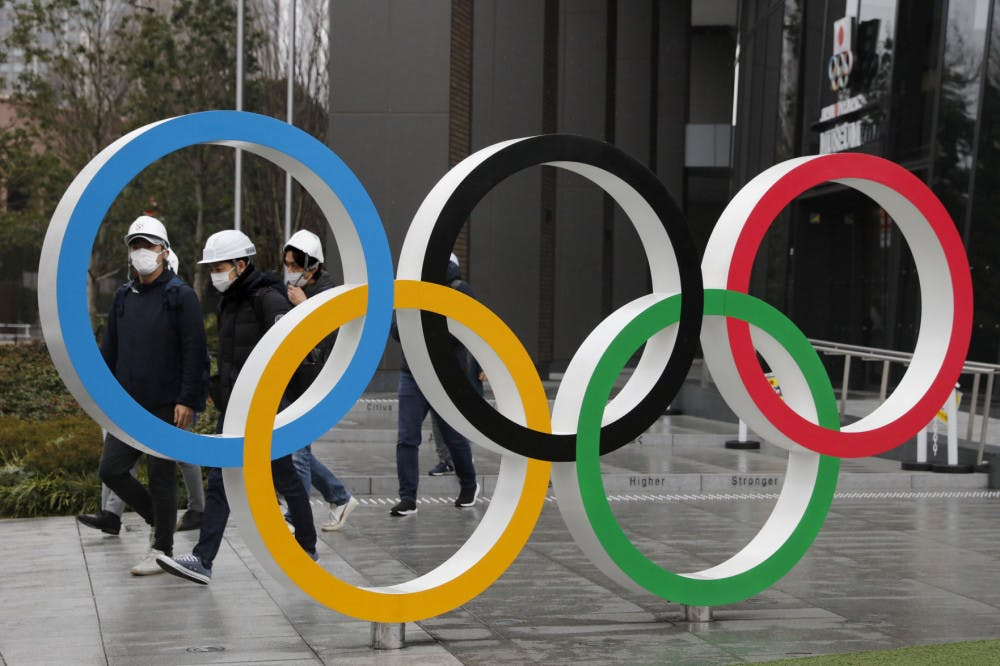 """<p>FILE - In this March 4, 2020, file photo, people wearing masks walk past the Olympic rings near the New National Stadium in Tokyo. It's been 2 1/2 months since the Tokyo Olympics were postponed until next year because of the COVID-19 pandemic. So where do the games stand? So far, many ideas about how the Olympic can take place are being floated by the International Olympic Committee, Japanese officials and politicians, and in unsourced Japanese newspaper articles coming from local organizers and politicians. The focus is on soaring costs, fans, or no fans, possible quarantines for athletes, and cutting back to only """"the essentials."""" (AP Photo/Jae C. Hong, File)</p>"""