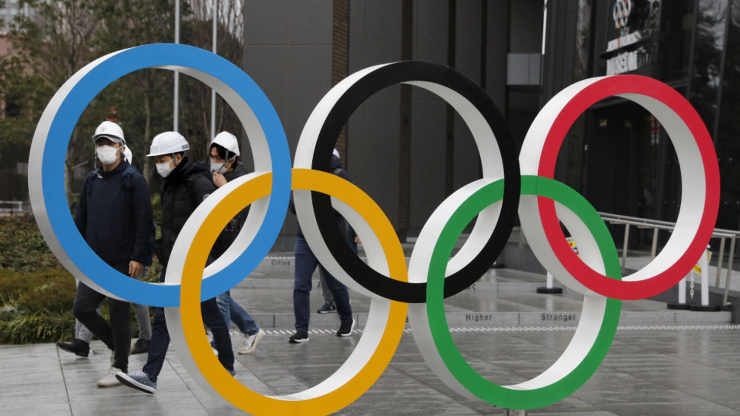 """FILE - In this March 4, 2020, file photo, people wearing masks walk past the Olympic rings near the New National Stadium in Tokyo. It's been 2 1/2 months since the Tokyo Olympics were postponed until next year because of the COVID-19 pandemic. So where do the games stand? So far, many ideas about how the Olympic can take place are being floated by the International Olympic Committee, Japanese officials and politicians, and in unsourced Japanese newspaper articles coming from local organizers and politicians. The focus is on soaring costs, fans, or no fans, possible quarantines for athletes, and cutting back to only """"the essentials."""" (AP Photo/Jae C. Hong, File)"""