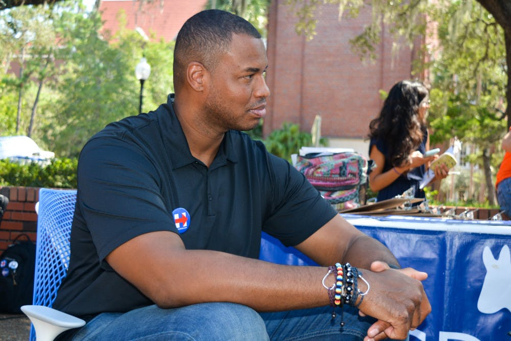 """<p dir=""""ltr"""">Jason Collins sits in front of the UF College Democrats table on Turlington Plaza on Friday. Collins, along with students, registered people to vote and campaigned for Hillary Clinton.</p>"""