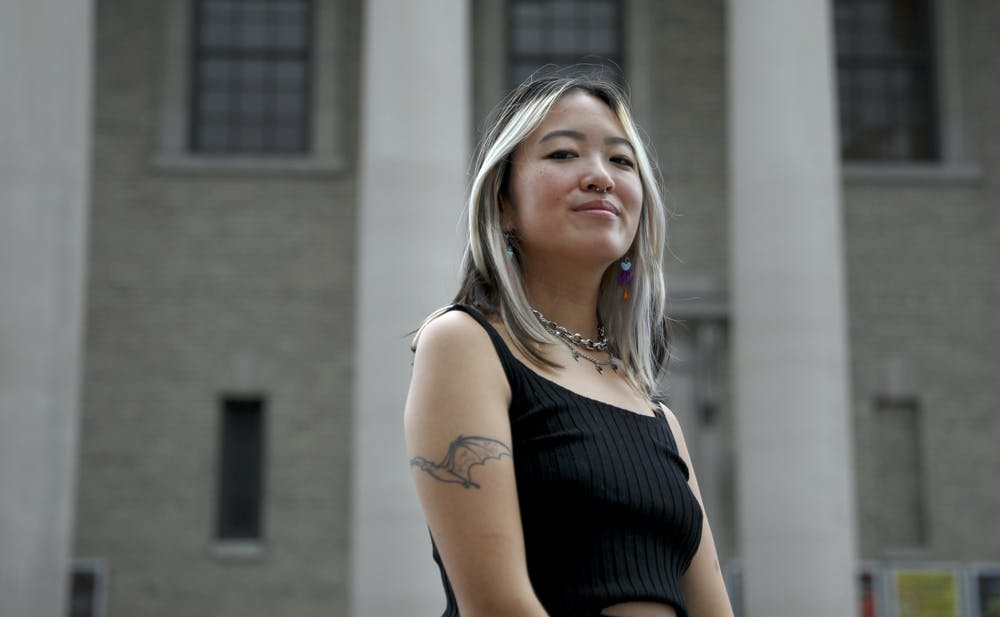 <p>Emily Lube, 22, a UF botany alumna, also known as DJ Smushyslugs, poses in front of Hippodrome Theater in Gainesville on Thursday, July 1, 2021.</p>