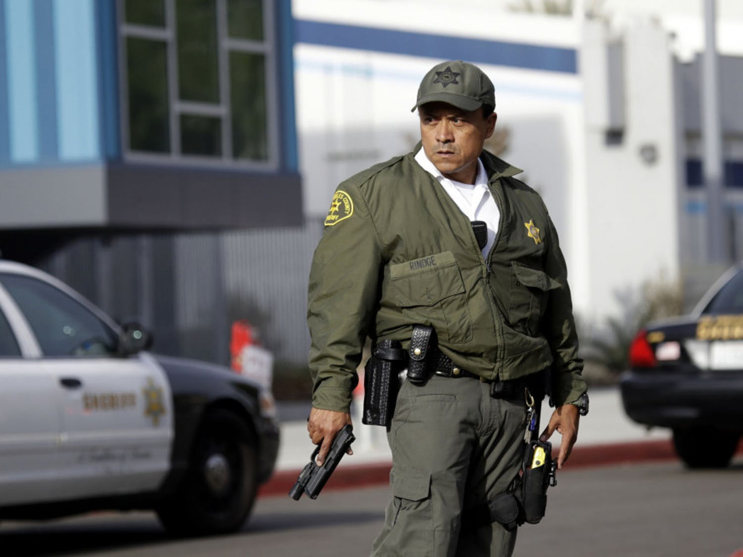 A member of the Los Angeles County Sheriff Department stands outside of Saugus High School with his weapon drawn after reports of a shooting on Thursday, Nov. 14, 2019, in Santa Clarita, Calif. (AP Photo/Marcio Jose Sanchez)