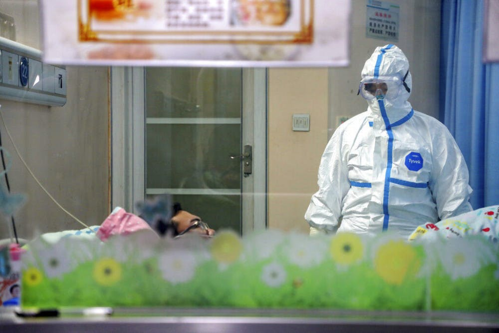 <p>A doctor attends to a patient in an isolation ward at a hospital in Wuhan in central China's Hubei Province, Thursday, Jan. 30, 2020. China counted 170 deaths from a new virus Thursday and more countries reported infections, including some spread locally, as foreign evacuees from China's worst-hit region returned home to medical observation and even isolation.</p>