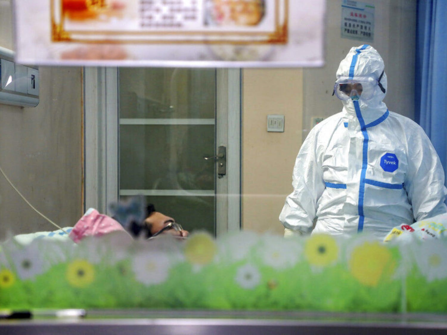 A doctor attends to a patient in an isolation ward at a hospital in Wuhan in central China's Hubei Province, Thursday, Jan. 30, 2020. China counted 170 deaths from a new virus Thursday and more countries reported infections, including some spread locally, as foreign evacuees from China's worst-hit region returned home to medical observation and even isolation.