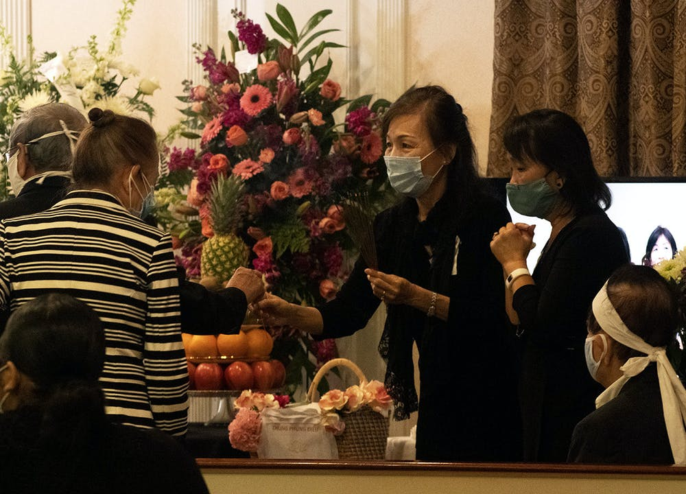 <p>Two people hand out sticks of incense during the funeral of Bach Lien Tong Duong on Wednesday, April 14, 2021. Duong was a volunteer who taught Vietnamese at UF before an official position was created and played a significant role in creating the annual Pho fundraiser for the Vietnamese Student Organization before she passed away.</p>