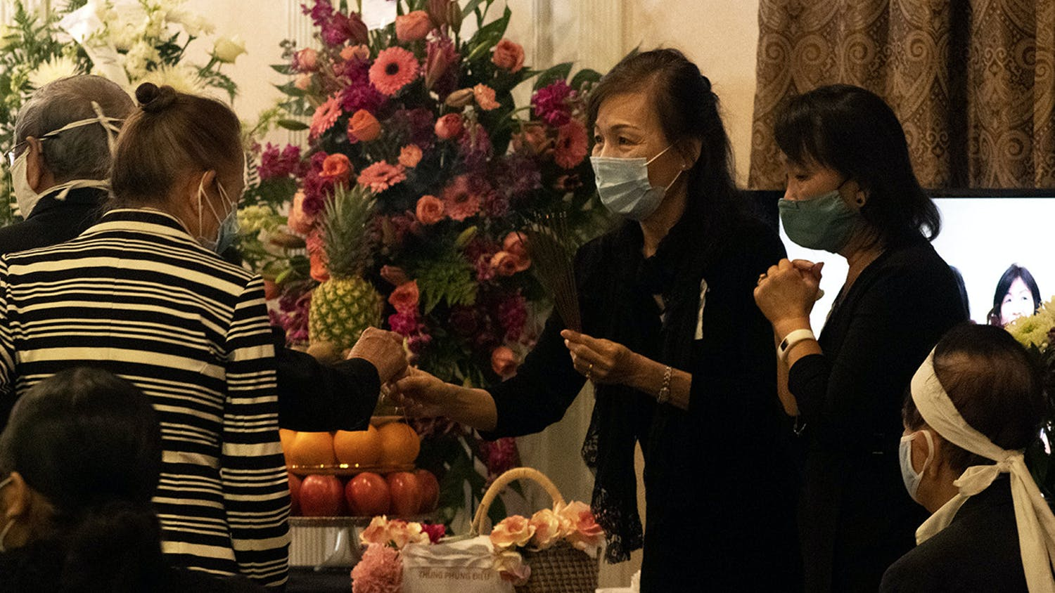 Two people hand out sticks of incense during the funeral of Bach Lien Tong Duong on Wednesday, April 14, 2021. Duong was a volunteer who taught Vietnamese at UF before an official position was created and played a significant role in creating the annual Pho fundraiser for the Vietnamese Student Organization before she passed away.